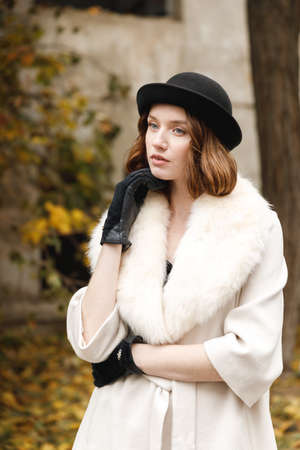 A young lady in a black hat and gloves and a light coat stands and looks outwardly. Retro. Outdoors. Stock Photo
