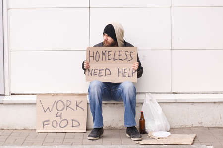 A beggar on the street sits with a sign about help. Outdoor.