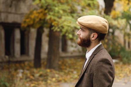 Gangster met een baard die in de afstand staren die zich dichtbij een verlaten gebouw bevindt. Retro. Buitenshuis. Stockfoto