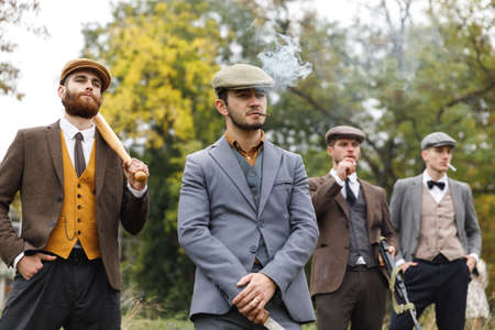 Four gangsters smoke among the trees. They hold several weapons in their hands. Retro. Outdoors.