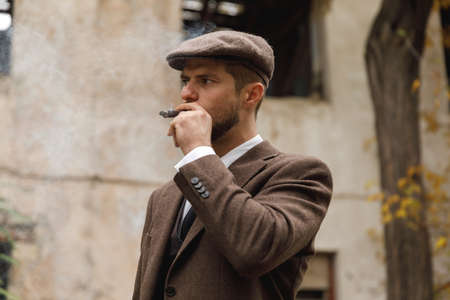 A man in a suit and hat smokes a cigar on the street . Retro. Outdoors. Stock Photo