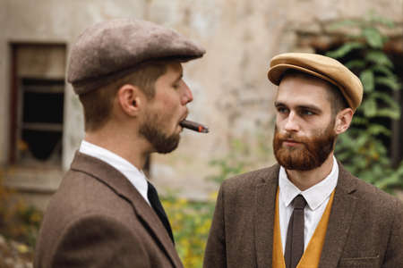 Two bearded gangstersstand on the street. One smokes a cigar, the other looks at it. Retro. Outdoors.
