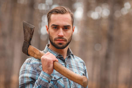 A guy holding an ax on his shoulder in an autumn forest Stock Photo