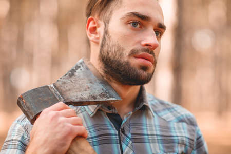 A guy with an ax in his neck in the autumn forest