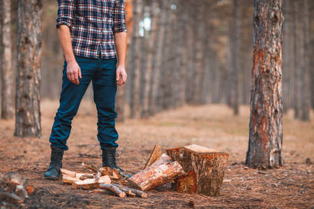 A man in a shirt is standing next to a chopped up close-up with his hands down in the autumn forest