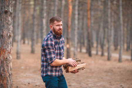 Man with firewood in his hands in the autumn forest