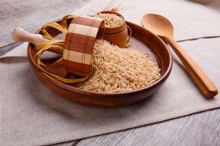 Samenstelling met rauwe rijst in een houten bruine kom met een houten lepel en een kleine kom. Op een grijze tafel bedekt met een linnen tafelkleed. Stockfoto