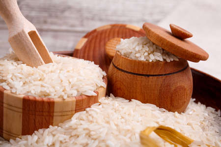 Raw rice in a wooden brown bowl with a wooden spatula and pot.