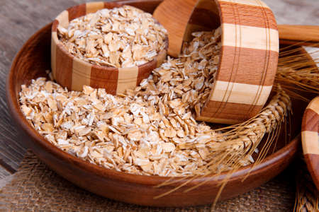 Composition with raw oat flakes in a bowl with a wooden spoon on a napkin sachet, on a brown wooden table. A sprig of wheat lies nearby. View from above. Stock Photo
