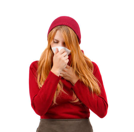 Redhead girl in red hat wiping her nose with a handkerchief on a white isolated background