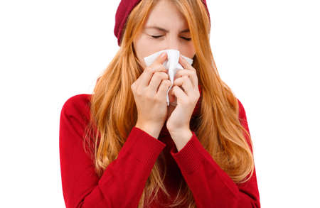 Redhead girl in red sneezes and wipes her nose on a white isolated background Stock Photo