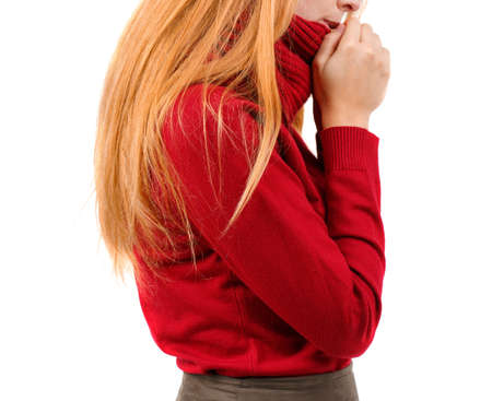A girl in a red sweater is holding hands by the mouth and stands sideways on a white isolated background