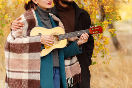 A girl is playing on a ukulele near a close-up guy on an autumnal blurred background Stock Photo