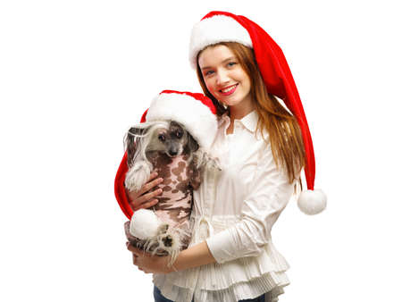 A girl is holding a Chinese Crested dog. A girl and a dog are dressed in a Santas red Santa hat. Isolated.