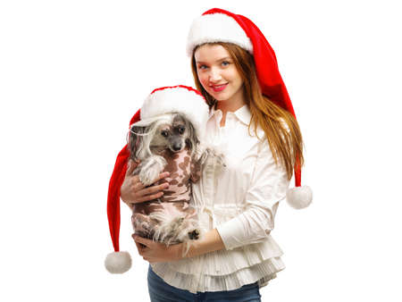 A girl and a dog are dressed in a Santas red Santa hat. A girl is holding a dog. Isolated on white background. Indoors. Stock Photo