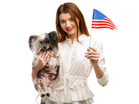 A girl in one hand holds an American flag and in her second hand holds a Chinese Crested dog. Isolated .