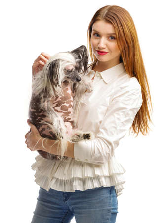 A young girl with dark hair is holding a small Chinese Crested dog. Isolated on white background. Indoors.
