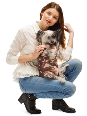 A beautiful girl planted her Chinese Crested dog on her knees. Isolated on white background. Indoors.