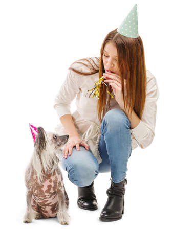 A girl blows a festive tune to her funny Chinese Crested dog. Isolated on white background. Indoors.