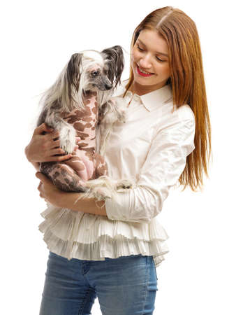 A young girl holds a funny Chinese Crested dog in her arms. Isolated on white background.
