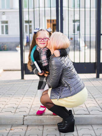 Mother takes her daughter from school, kisses daughter, Family concept