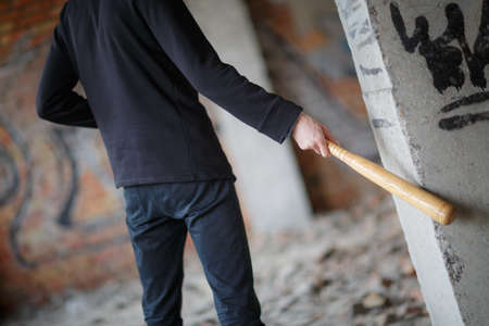 A street hooligan at a construction site hit a batted column with graffiti. Stock Photo