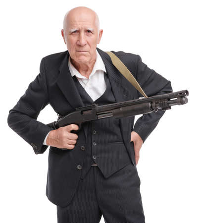 Elderly grandfather in suit holds a shotgun in his hand with screwed up eyes isolated on white background