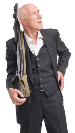 Elderly grandfather in suit holds in hand a shotgun laying it on shoulder, looking up isolated on white background Stock Photo