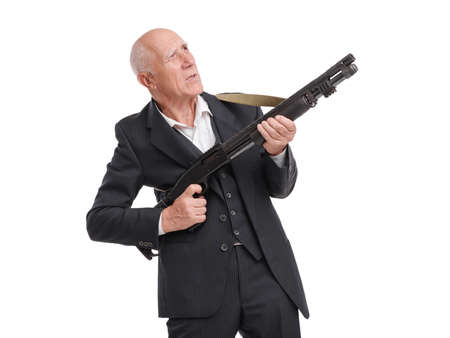 Elderly grandfather in a suit holds a shotgun looking away, aiming, isolated on a white background 版權商用圖片