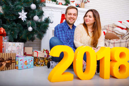 Close-up of a young married couple at christmas with figures 2018