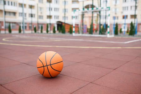 Basketball, a bright, new ball lies on the red, rubber coating of the stadium.