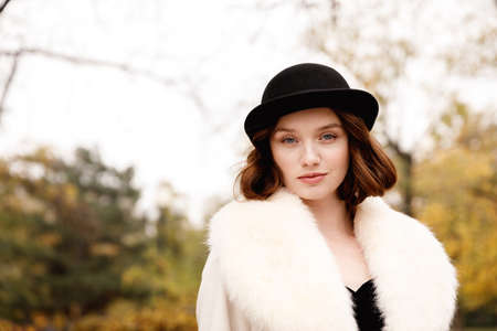 Portrait of retro girl in black hat, fur coat and black gloves in autumn park