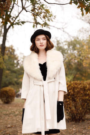 Retro gangster girl in black hat and coat in autumn park looks aside Stock Photo