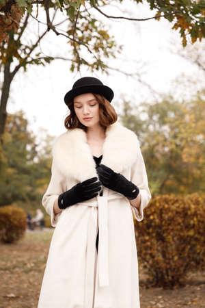 Retro gangster girl in black hat, fur coat and black gloves in autumn park
