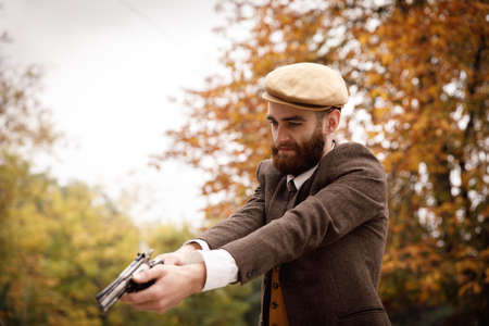 Retro gangster in a suit and a cap in the park with a gun.