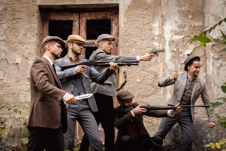 A group of gangsters with a dangerous weapon in their hands against the background of the old abandoned building. Retro. Stock Photo