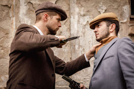Gangsters on the background of an old abandoned building a man wants to put a knife to his throat.
