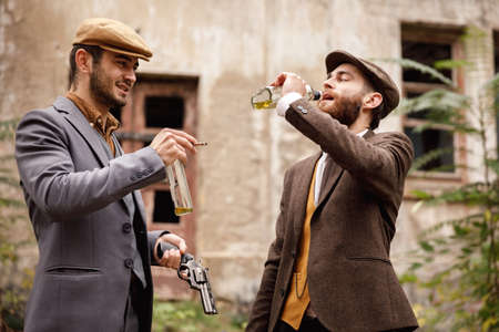 Gangsters on the background of the old abandoned building drink alcohol. In the hands of arms Stock Photo