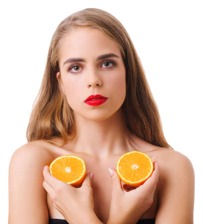 Serious girl with two halves of orange on white isolated background