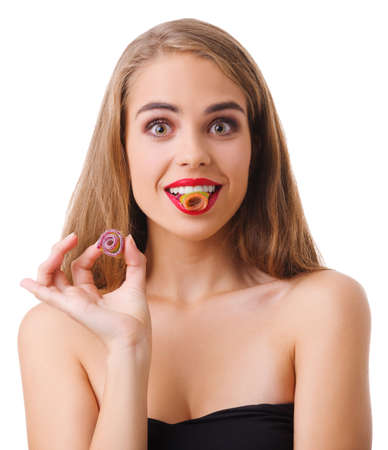 Joyful girl holding a tooth in her teeth on a white isolated background Stock Photo