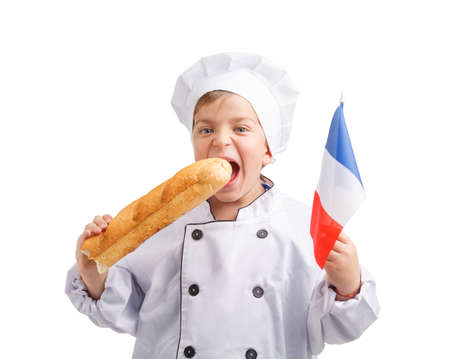 A small chef bites a baguette with a French flag in his hand on a white isolated background