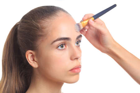 A girl put a foundation on the forehead on a white isolated background
