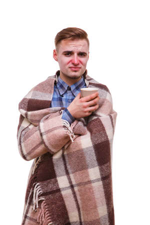 Sick guy shivering with a drink in his hand on a white isolated background