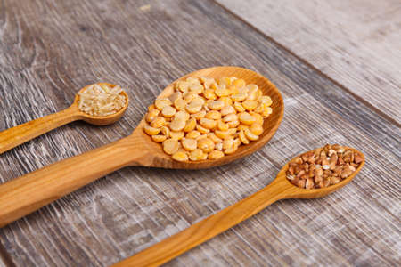 Three wooden spoons are filled with cereals on the table
