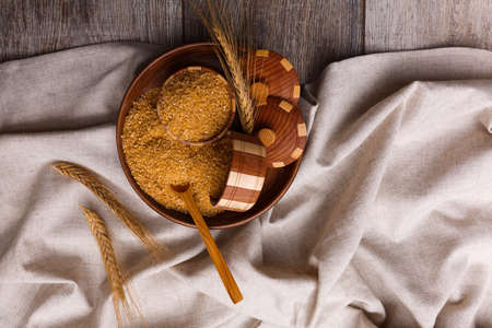 Corn porridge in a wooden plate with wheat spikes on a cloth on a close-up table Stock Photo - 89911925