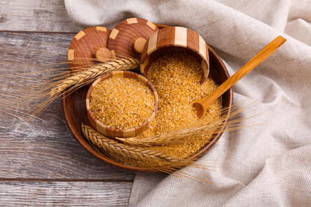 Wheat porridge in a wooden dish with a wooden spoon in a porridge on a table with a cloth