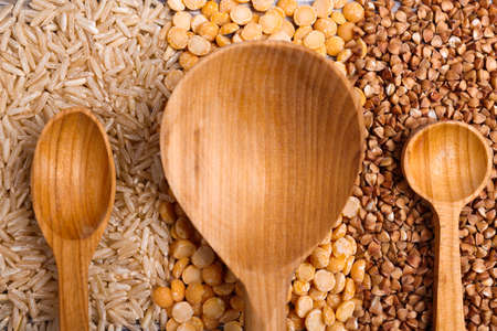 Three spoons of wooden close-up on a background of cereals Stock Photo - 89912093