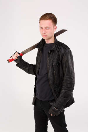 A guy stands and holds a machete on his shoulder. Isolation.