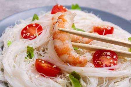 Pasta made from rice noodles and prawn which is eaten with sticks. Indoors. Close-up.