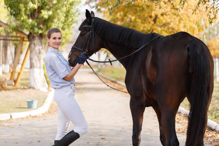 A female rider stands near a dark horse and holds a harness. Outdoors.